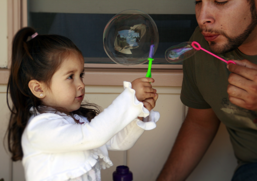 Little girl blowing bubbles with uncle